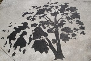 Tree design in concrete, darker than the rest of the concrete.