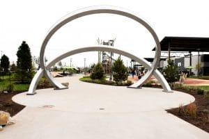 Sandscape® flatwork under circular sculpture next to playground