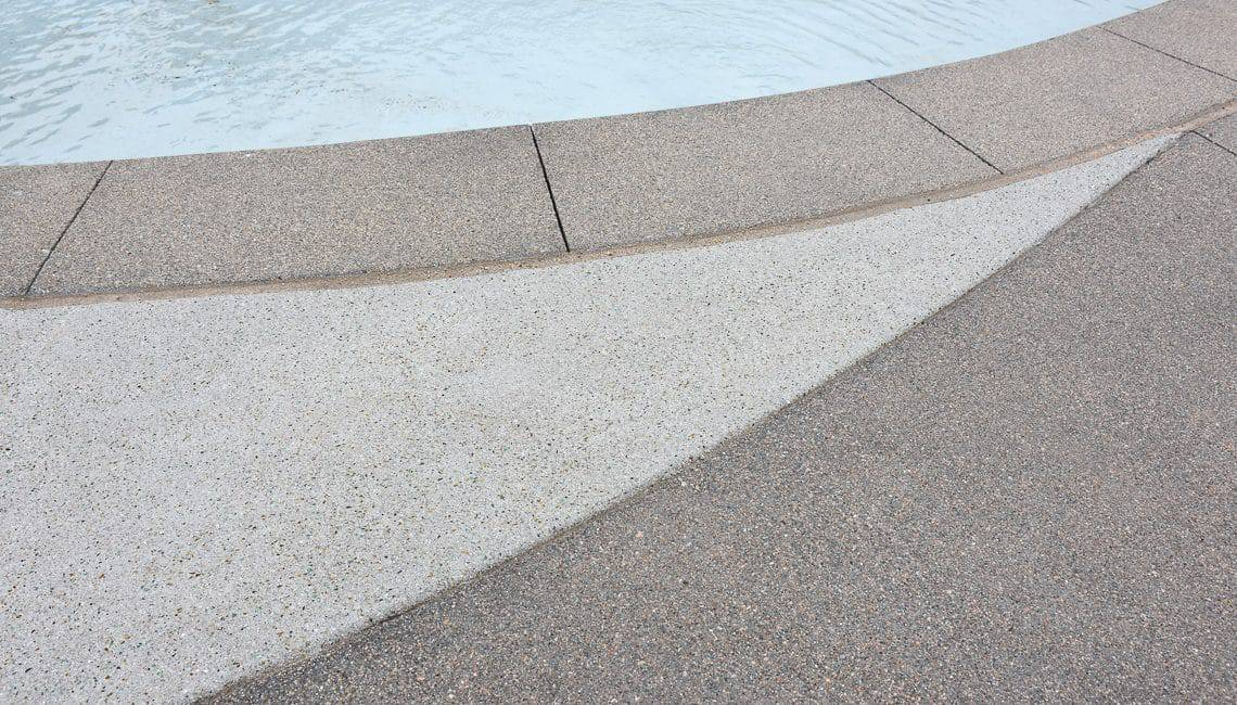 Up close perspective of Sandscape Refined coping and pool deck at apartment complex.
