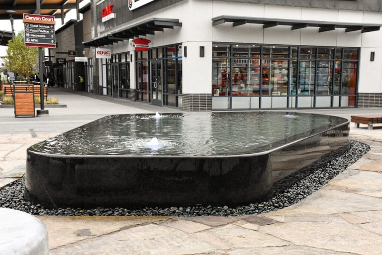 Sleek, architectural water feature at outlets with shops in the background.