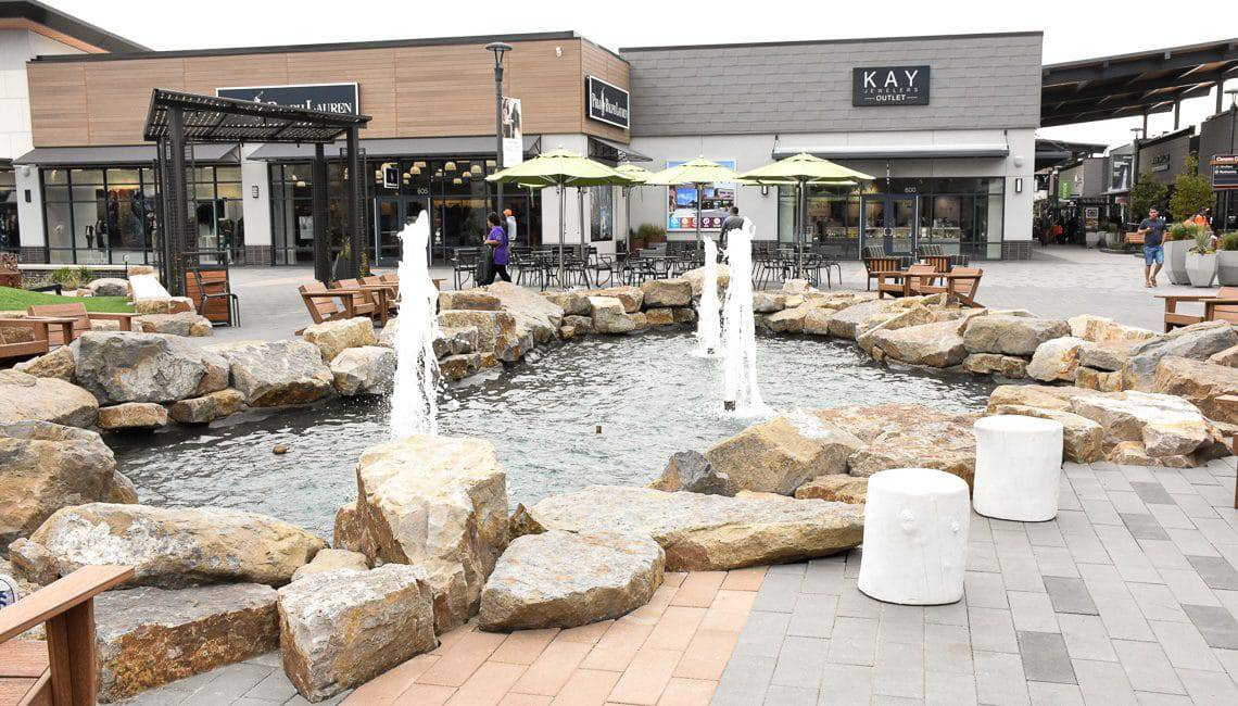 Water feature at outlets surrounded by natural boulders.