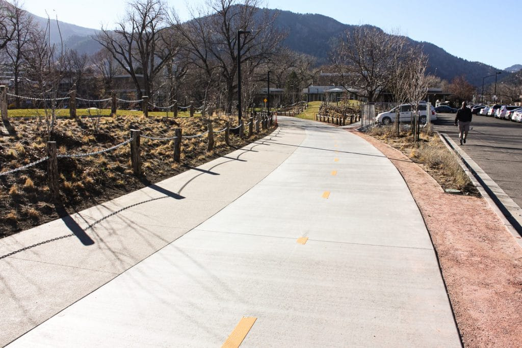 Broom finished bike path next to sandscape walkway.