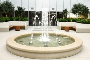 Water feature with concrete basin and nine spray nozzles