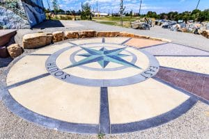 Compass rose created out of different concrete textures, colors and style create public art in the parks