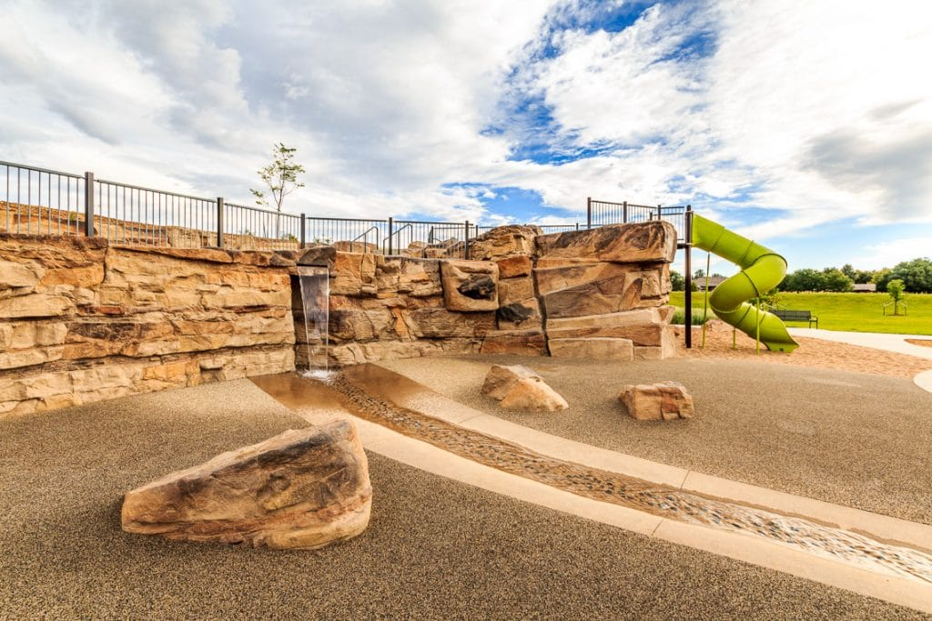 Park with rockwork and stream bed next to playground.