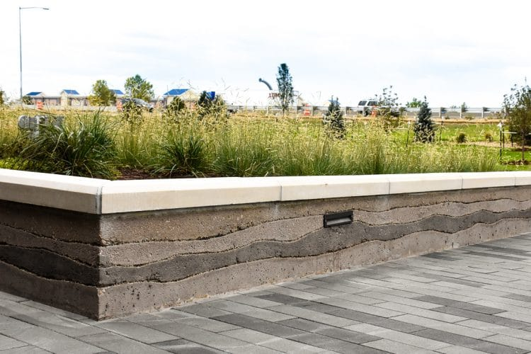 Sedimentary planter walls create a unique layered look around these planter beds.