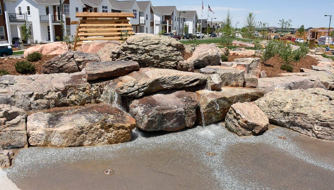 Natural boulder waterfall at stream bed in Colorado neighborhood constructed by Colorado Hardscapes.