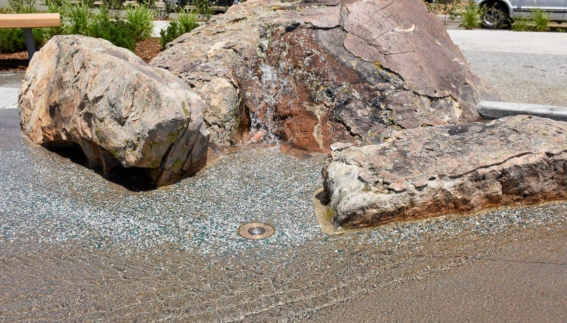 Lithocrete stream bed next to natural boulders, a beautiful decorative concrete feature in Denver Colorado.