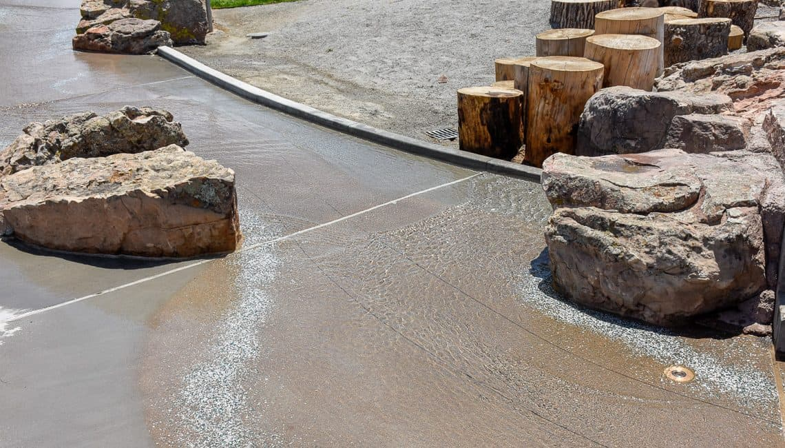 View of natural boulders and lithocrete with running water in a stream bed on a hot day installed by Colorado Hardscapes.