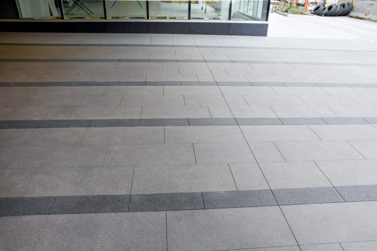 Using a paver alternative Colorado Hardscapes creates a running bond pattern with colored bands.