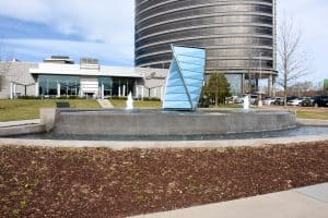 Front view of Denver Tech Center water feature with three geyser nozzles and a large prism centerpiece in front of Shanahan's Steakhouse.