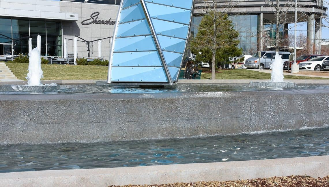 Up-close photo of Denver Tech Center water feature with three geyser nozzles and a large prism centerpiece.