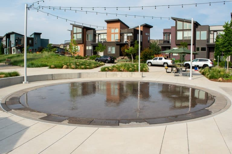 Buffalo Wallow Splash Pad with surrounding planter walls, benches, and lights strung across. Splash Pad done by Colorado Hardscapes.