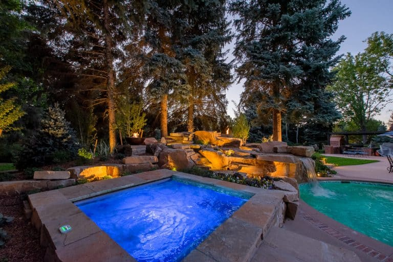 Dream backyard at private residence with RGB lighting in spa and sandstone waterfall.