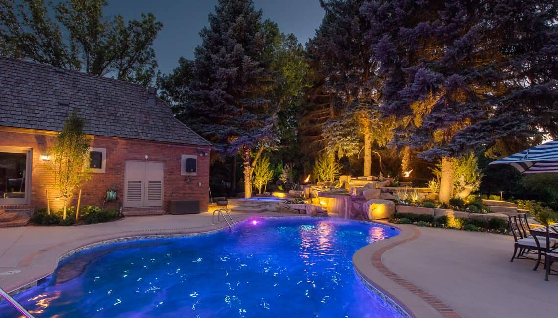 Dream backyard at private residence with sandstone waterfall, spa, and pool with fiber optic lighting.
