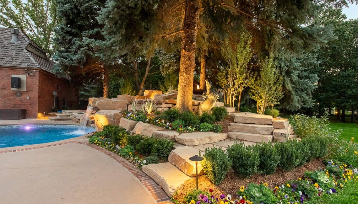 Dream Backyard at private residence with sandstone stepping stones leading to sandstone waterfall.